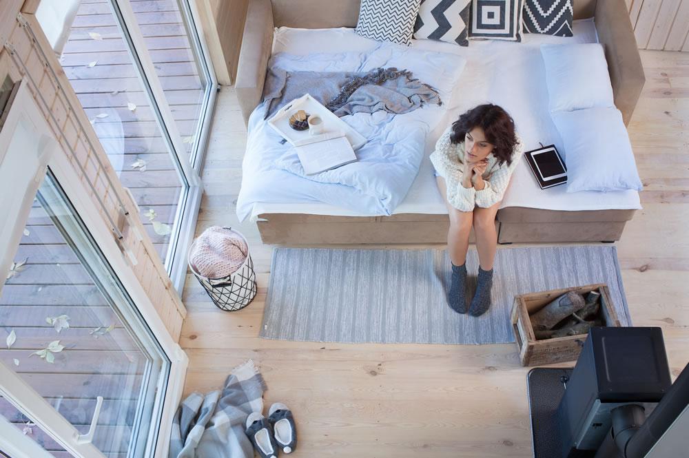 vrouw eenzaam in slaapkamer op bed zittend